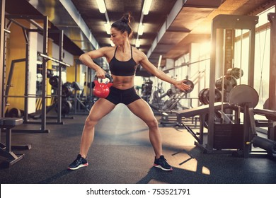 Fit young woman on training in gym using kettle bell weight for shaping arm muscles