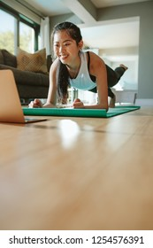 Fit young woman in plank position repeating online instructions by coach on laptop. Fitness woman working out at home watching video tutorial on laptop.