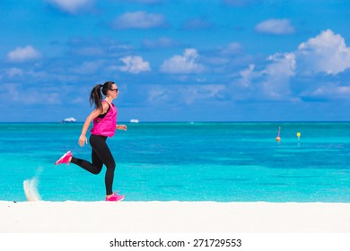 Fit young woman running along the tropical beach in her sportswear