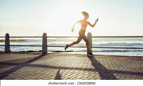 Fit young woman in running fast over a seaside promenade. Side view of female runner sprinting during sunset.