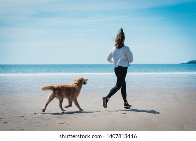 Fit Young woman running with her dog on the beach