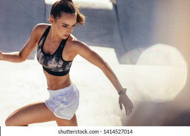 Fit young woman running in morning. Health conscious woman doing running workout outdoors.