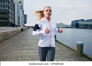 Fit young woman running on the boardwalk along river. Caucasian female athlete training outdoors by the waterfront.
