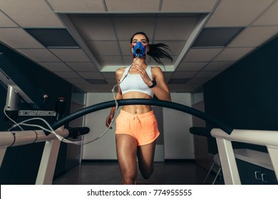Fit young woman running on treadmill with a mask. Athlete examining her performance in sports science lab.
