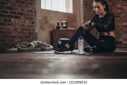 Fit young woman sitting on a floor and looking at her smartwatch at fitness studio. Athlete looking at her performance on smartwatch fitness app after workout.