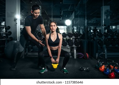 Fit young woman in sportswear focused on lifting a dumbbell during an exercise class in a gym