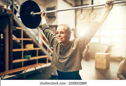 Fit young woman in sportswear smiling while lifting weights above her head during a workout session in a gym