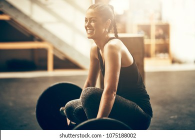 Fit young woman in sportswear smiling while preparing for a workout session with heavy weights in a gym