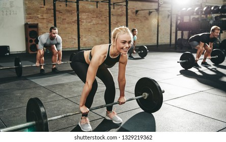 Fit young woman in sportswear smiling while lifting barbells during a weightlifting session with others at the gym