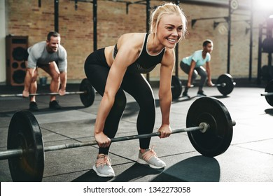 Fit young woman in sportswear smiling while preparing to lift weights during a weightlifting session at the gym