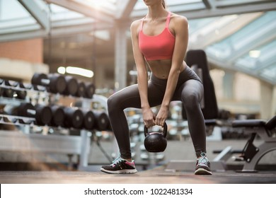 Fit young woman squatting while standing on the floor and holding heavy kettlebell between legs during training