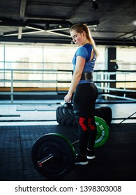Fit young woman standing by barbell with weight plates getting ready to lift it during weightlifting training in gym