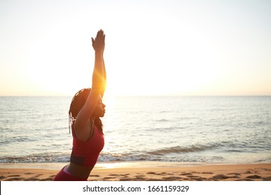 Fit young woman standing in morning sun rays and practicing warrior pose