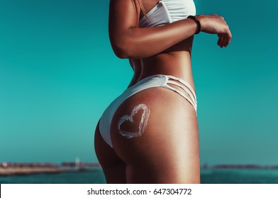 Fit young woman in summer applying sunscreen protection on the beach for Sun care