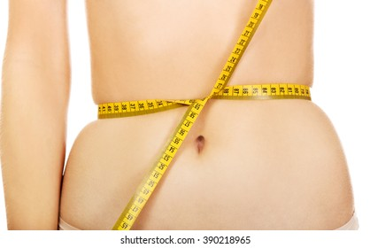 Fit young woman tied measure tape on her belly