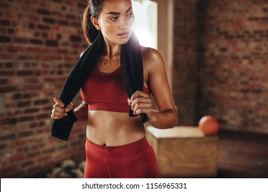 Fit young woman with a towel at health club. Female relaxing after workout.