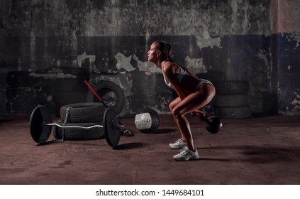 Fit young woman training hard with the kettlebell weight in the garage or warehouse. Tires, bar, metbol, crossfit . Fitness, functional, training, and lifestyle concept