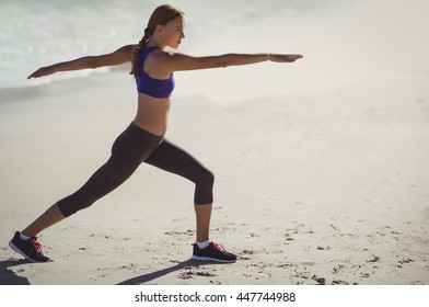 Fit young woman warming up on beach