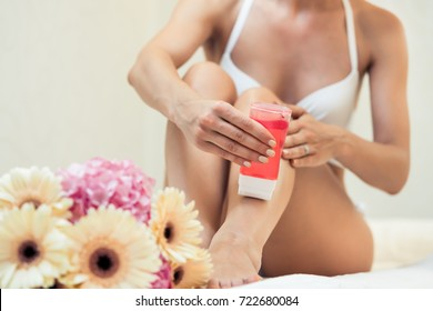 Fit young woman waxing her legs with a portable roll-on depilatory wax heater for painless hair removal at home