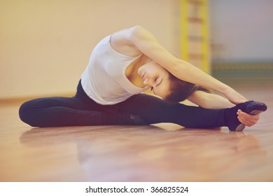 fit young women doing stretching exercises in fitness studio