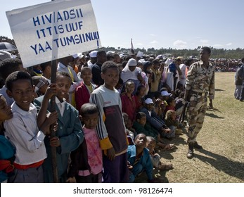 FITCHE - JANUARY 13: unidentified Children holding an HIV banner, with an Ethiopian Soldier with a gun behind them at the 20th World Aids Day event on January 13, 2008 in Fitche, Ethiopia