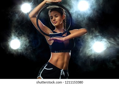 Fitn woman athlete holding gym equipment on black background. Studio shot.