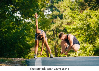 Fitnes and healthy couple exercising on the road near the forest