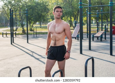 Fitnes man posing on street fitness station showing his muscular body