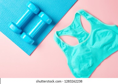 Fitnes minimalism concept. Dumbbells and sport bra on blue and pink backgroundm top view