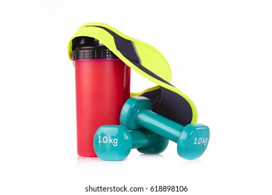 Fitnes symbols - tennis headband capa on red bicycle water bottle with two blue vinyl coated dumbbells on white background