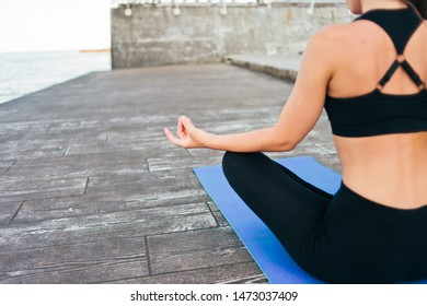 Fitnes Woman meditates sitting on a yoga mat on the beach. View from the back. The concept of internal balance. Crop photo