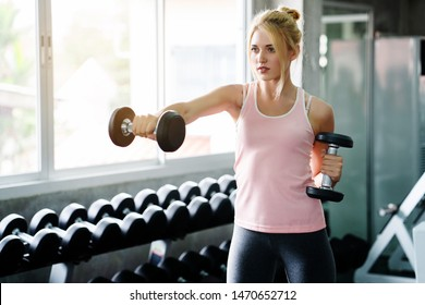 Fitness activities in the Caucasian women's gym The action of lifting dumbbells to keep the arm muscles tight and strong Daily exercise makes the body relax. Good mental health Beautiful shape