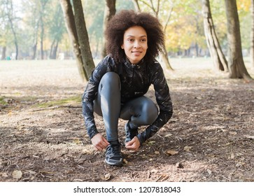 Fitness African woman ready for running in forest, female runner tying shoe laces after training. Looking forward.