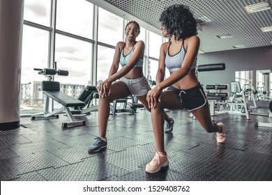 Fitness african women doing lunges exercises for leg muscle workout training in gym. Active black girls doing front forward one leg step lunge exercise. Weightloss pilates concept
