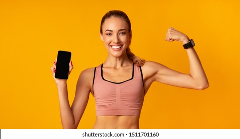 Fitness App. Sporty Girl Holding Smartphone With Blank Screen Showing Arm Muscles On Yellow Background. Panorama, Mockup
