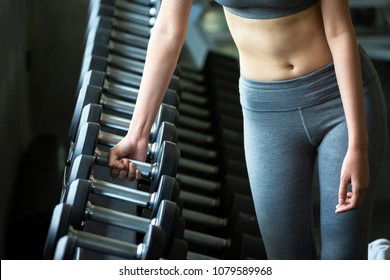Fitness asia woman doing exercise and lifting dumbbell weights in sport gym, healthy lifestyle concept