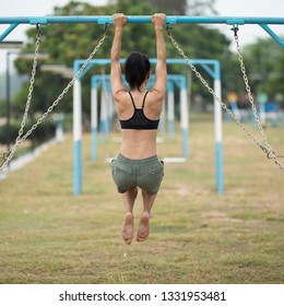 Fitness asian woman doing pullups at outdoor fitness park, healthy lifestyle  concept.