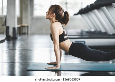 Fitness asian woman doing yoga exercise and relax with sportswear in sport gym, healthy lifestyle concept
