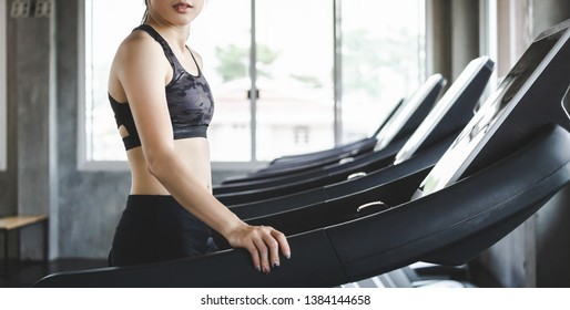 Fitness asian woman with sportswear running on treadmill machine in sport gym
