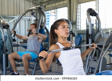 Fitness Asian woman working out shoulder pull down at gym. Girl strength training using lat pulldown machine.