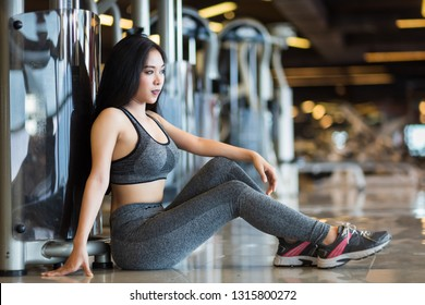 Fitness Asian women sitting in sport gym interior and fitness health club with sports exercise equipment Gym background.