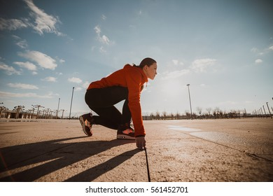 Fitness athlete on starting near stadium track preparing for a sprint. Fitness, healthy lifestyle concept.Ready to run position