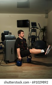 Fitness athletic man in electrical muscular stimulation suit doing L-Sit plank on weights in gym