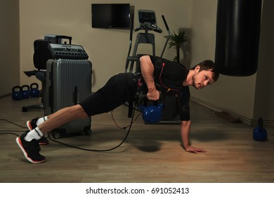 Fitness athletic man in electrical muscular stimulation suit lifting weights in gym