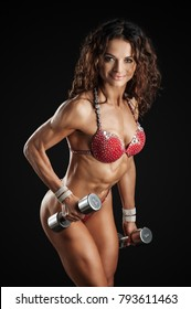 Fitness athletic woman in red bikini with dumbbells showing muscles. Isolated on black background