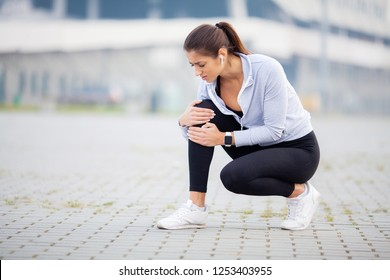 Fitness. Athletic women holding knee having a trauma