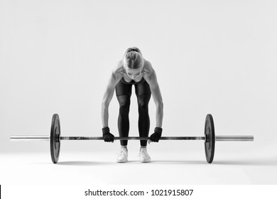 Fitness attractive woman preparing to practice deadlift with heavy weights Female bodybuilder doing heavy weight lifting work out on white background Black and white horizontal picture