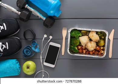 Fitness background, blue sport equipment for training and fruit salad, copy space, top view. Weightloss, active lifestyle, healthy food concept
