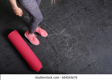 Fitness background, copy space, sport urban style, slim female legs, yoga mat, gray background