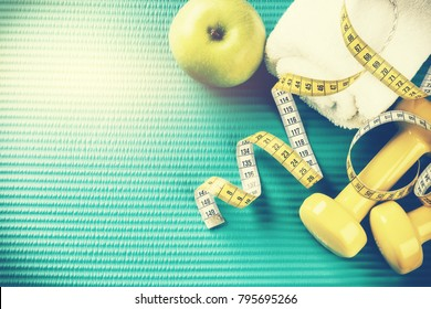 Fitness background with dumbbells, measuring tape and towel. Healthy lifestyle concept with copy space